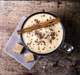 frothy-cup-of-espresso-coffee-with-cinnamon-topped-with-sprinkled-chocolate-on-old-wooden-background_142922332